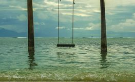 Swing set up in the water at tropical island beach with an amazing beautiful view to the sea and the mountains in Summer holidays. Relax and tourist travel royalty free stock photo