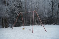 Swing set in the winter. Not being use covered in frost with snow on the ground trees in the back ground stock photography