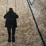 Swing Shadow. Shadow of a girl riding on a swing royalty free stock photos