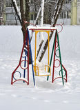 Swing in the snow in courtyard Stock Photo
