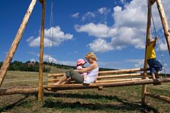 Swing in the summer. Woman and two children playing on a wooden swing outdoors under a bright blue summer sky stock images