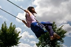 Kid on swing in open air royalty free stock photos