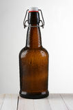 Swing Top Beer Bottle Light to Dark. A swing top beer bottle against a light to dark background. The brown bottle is on a rustic whitewashed wood table. Vertical Stock Image