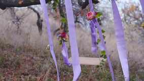 Swing on tree decorated with flowers, blue ribbon with red flowers, wind shakes the beautiful swing. Swing on a tree decorated with flowers, blue ribbon with red stock footage