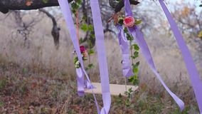 Swing on tree decorated with flowers, blue ribbon with red flowers, wind shakes the beautiful swing. Swing on a tree decorated with flowers, blue ribbon with red stock video
