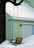 Swing on tree in winter yard Royalty Free Stock Images