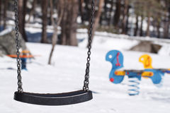 Swing in Winter. One swing in the foreground and other swings behind. In winter scene with snow Royalty Free Stock Photo