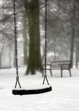 Swing in winter. Abandoned swing in winter, covered in snow Royalty Free Stock Images