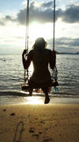 Swing. Womans silhouette on a swing at the beach Stock Photos