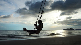Swing. Woman's silhouette on a swing at the beach Stock Photos