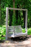 Swing in the woods. A wooden swing for resting in the woods Royalty Free Stock Images