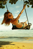 Swing. Young happy woman having fun on a swing on a tropical beach Stock Image
