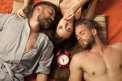 Swinger relations, relax, wake up. Men and women with long hair, lover. Family trust, polygamy, betrayal. people lovers sleep at alarm clock, time. Love stock photo