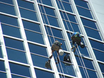 Swingers. Need a good sense of balance for this job... window washers, hard at work on a skyscraper Royalty Free Stock Image