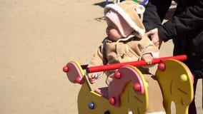 Swingin del bebé en el oscilación del caballo almacen de metraje de vídeo