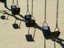 Swinging. Row of empty swings on playground royalty free stock photos