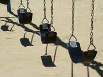 Swinging. Row of empty swings on playground Royalty Free Stock Photos