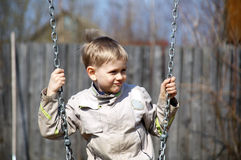 Swinging. Happy young boy on a swing Stock Photo