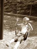 Swinging. Little girl playing on a swing.  Sepia tone image Royalty Free Stock Photography