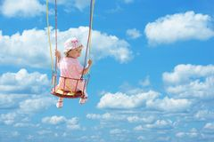 Swinging. Happy cute child swinging in blue summer sky Royalty Free Stock Photos