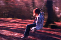Swinging. A girl on a swing in a forest Royalty Free Stock Photos