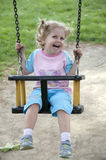 Swinging. A little girl is swinging in a swing royalty free stock image