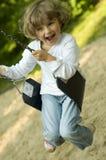 Swinging. Little girl swinging on the park royalty free stock image