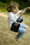 Swinging. Happy cute girl swinging on the park royalty free stock images