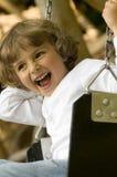 Swinging. Happy cute girl swinging on the park stock photo