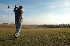 Swinging away. A golfer gets an early start on the season at a driving range royalty free stock image