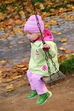 Swinging baby. Swinging small girl in autumn park Royalty Free Stock Image