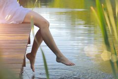 Swinging bare feet of woman sitting on pier. Summer vacation. At the lake stock image