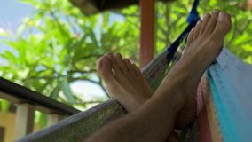 Swinging bare man feets in a hammock on terrace. Vacation on Koh Tao Tanote Bay, Thailand