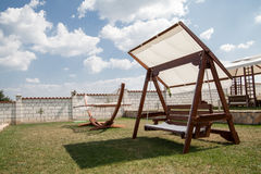 Swinging bench and hammock in the garden. Stock Image