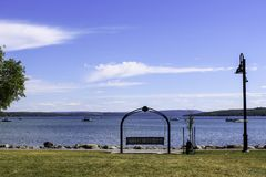 Swinging bench on the shoreline of Canandaigua Lake. Sunny day and calm water on the lake. Rocks on the shoreline. Boats on the lake stock image
