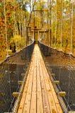 Swinging bridge in fall Royalty Free Stock Photos