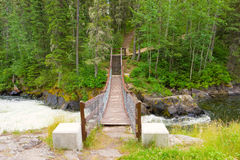 A swinging bridge over a river at a provincial park in canada. A wobbly crossing over cascading water as experienced on a nature hike through a forest stock images
