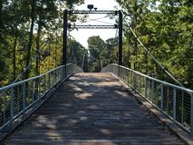 Swinging bridge over a river. A renovated swinging bridge over a river in Byram, MS. The bridge was originally built around 1908 Royalty Free Stock Image