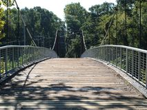 Swinging bridge over a river Stock Photography