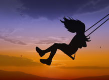 Swinging child. Silhouette on sunset background Stock Images