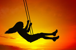 Swinging child. Silhouette on abstract sunset background Stock Photo