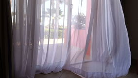 Swinging curtain on the wind in hotel resort room. With opened door to garden stock footage