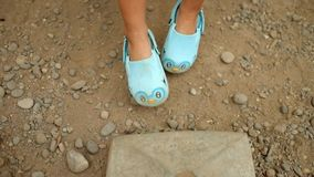 Swinging feet video. Close up view swinging feet touch dirt stock footage