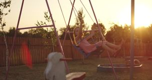 Swinging girl in playground. Wide shot of of a swinging girl in a playground stock video footage