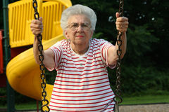 Swinging Grandmother 10. Senior citizen woman sitting on a playground swing royalty free stock photography