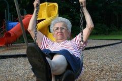Swinging Grandmother 12. Senior citizen woman on a playground swing royalty free stock image