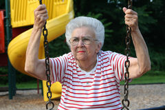 Swinging Grandmother 9. Senior citizen woman sitting on a playground swing, pensive expression royalty free stock photography