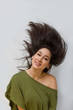 Swinging hair. Beautiful woman in a green shirt swinging her dark brown hair straight up, isolated on white royalty free stock images