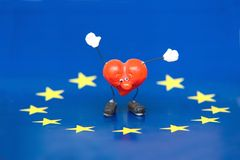 Swinging Heart. A toy heart with swinging hands, on a European Union flag stock photography