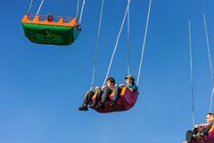 Swinging high in the air in the whirligig. stock images